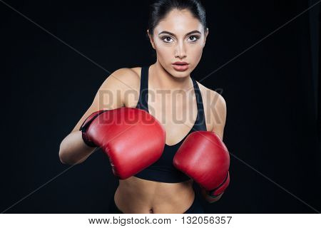 Fitness girl in boxing gloves fighting on black background