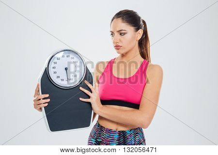 Sad fitness woman holding weighing machine isolated on a white background