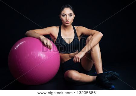 Beautiful young fitness woman sitting and posing with purple fitball over black background