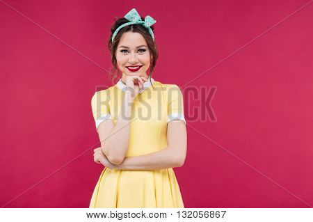 Portrait of smiling beautiful young woman in yellow dress with blue headband over pink background