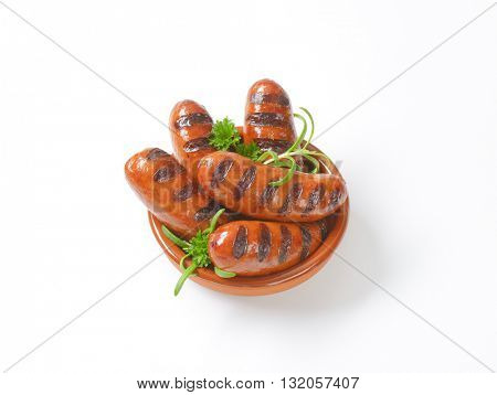 bowl of grilled short sausages on white background