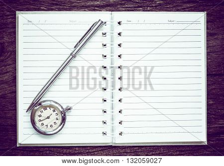 Antique pocket watch on notebook for notes On old textured wood. Vintage style.