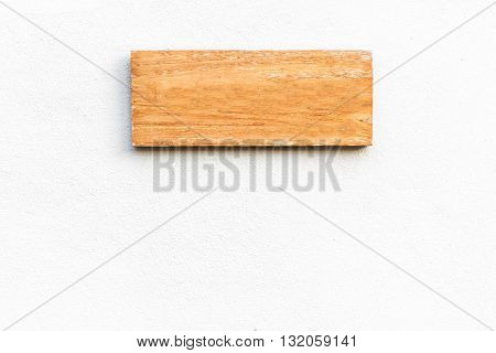 blank wooden sign on white concrete wall.
