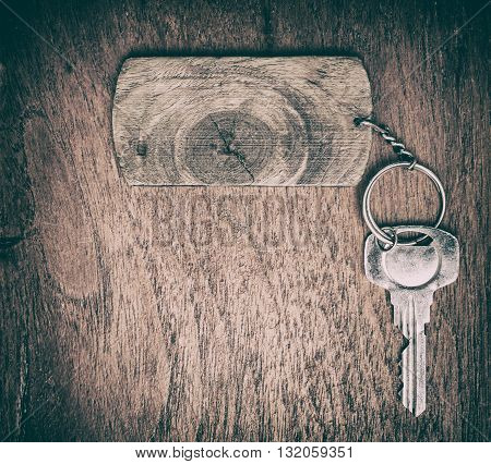 wooden signs with key chain on wooden background.