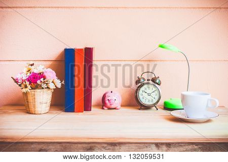 Office desk workplace with books and alarm clock on the wooden table.