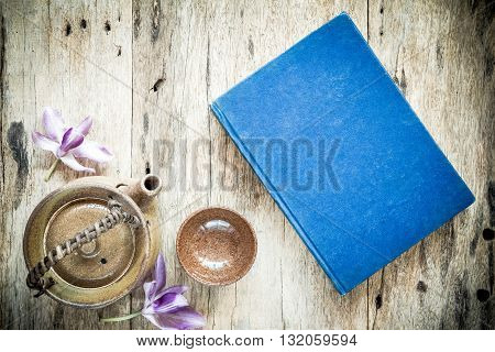 Teapot and blue book on old wooden background