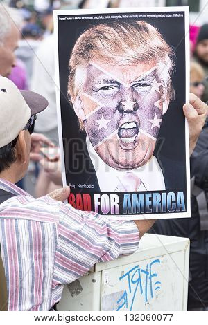 SAN DIEGO USA - MAY 27 2016: A protester holds a sign featuring a picture of Donald Trump superimposed with the confederate flag at a protest outside a Trump rally in San Diego.