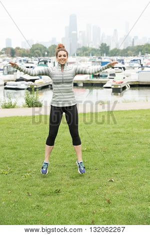 A beautiful sexy girl doing workout inside a park. Few boats and high rise buildings is be seen at the background.
