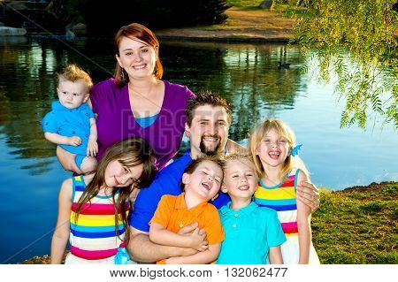 Portrait of a large family with five young children. All are dressed in bright colors and they are standing by a lake. Most have big smiles or are laughing.