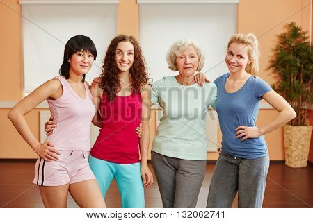 Team of women at fitness studio with senior lady