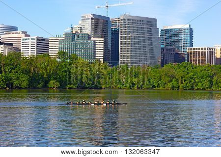 Rowing on Potomac River in the morning. Sunrise over the skyscrapers in Washington DC USA.