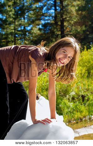 A smiling girl climbs on a block of ice on a sunny day. She is wearing a sleevless shirt and a big smile.