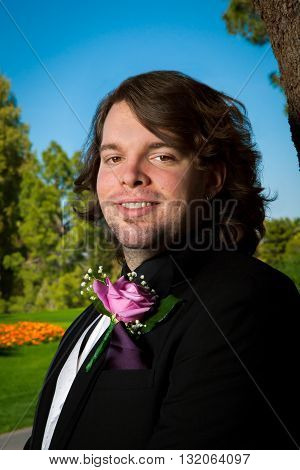 Outdoor portrait of a groom on his wedding day. He stands smiling at the camera with a rose boutonniere stubble earrings and long hair. Vibrant colors.