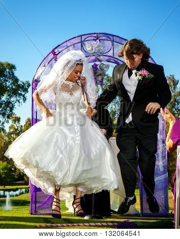 A bride and groom jump the broom as part of their wedding ceremony.