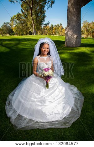 A beautiful African American bride kneels for a portrait before her wedding. She is surrounded by lush green grass and holds her rose bouquet.