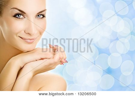 Beautiful young woman over abstract blue background