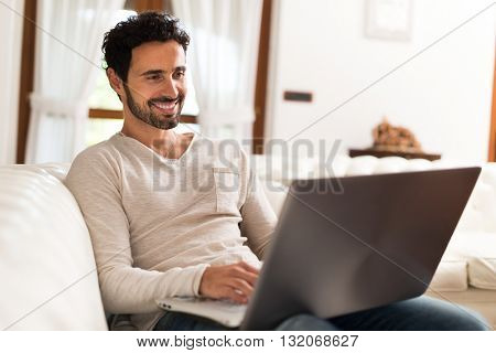 Man using a laptop while sitting on the couch in his living room
