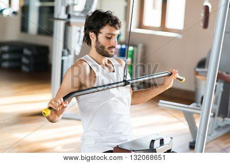 Muscular man training hard in a gym