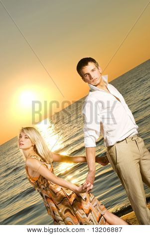 Young couple dancing near the ocean at sunset