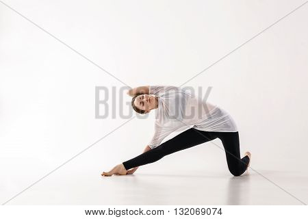 Young woman doing yoga exercise in the white room