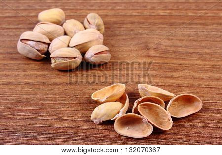 Roasted pistachio nuts with shells on natural wooden table background healthy food and nutrition