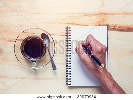 Drink coffee and write notebook on office dask