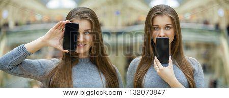 Young brunette women covers her face screen smart phone, indoor