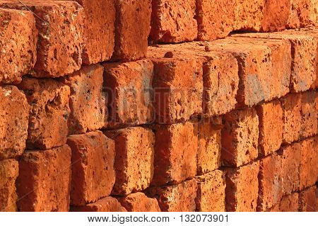 A background of a stack of red bricks at a construction site.