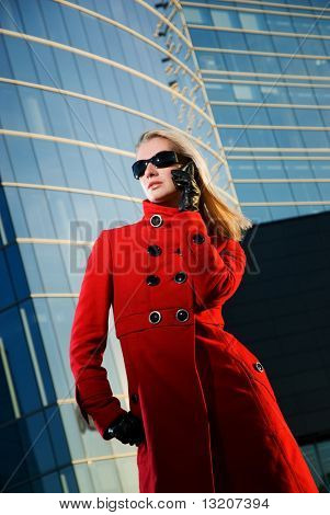 Beautiful young blond talks on the phone. Modern building behind her