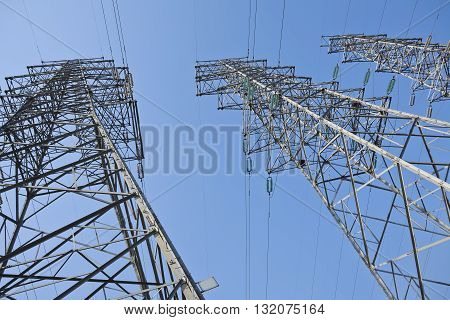 look up at  high-voltage power transmission towers