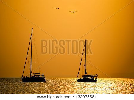 Romantic sunset over the sea - two boats floating and two birds flying.