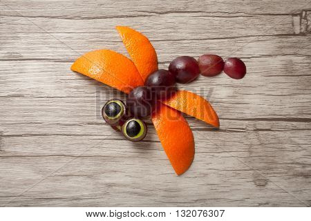 Funny dragonfly made of fruits on board
