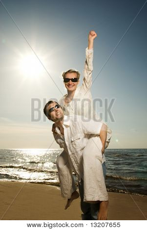 Handsome young man giving his girlfriend piggyback ride near the ocean at sunset