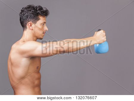 Young fitness male exercise with kettle bell on grey background