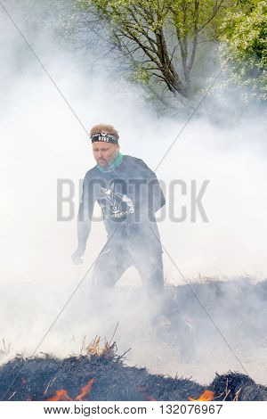 STOCKHOLM SWEDEN - MAY 14 2016: Man in black clothes running through fire and smoke in the obstacle race Tough Viking Event in Sweden April 14 2016