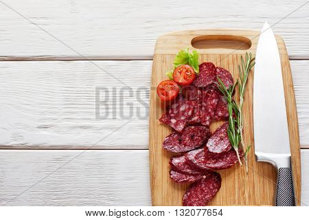Cutting board with sliced appetizing sausage on white background. Closeup of sliced sausage on wooden cutting board. Copyspace, void. Flat lay of vertical position of board with sausage