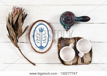 Flat lay of rustic clay dishes for tea. Tea utensil composition with flower on white wooden background. Teapot, two cups on saucer, plate and flower on white table closeup