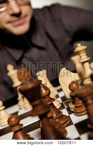 Chess master thinking before making a move (shallow Dof, focus on chess piece)