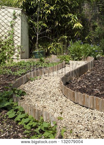 English summer garden with gravel winding pathway leading to white painted shed