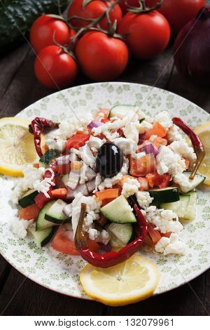 Shopska salad with cheese, olives, tomato, cucumber, onion and chili peppers