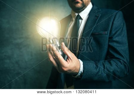Business creativity and vision concept with elegant adult businessman holding bright light bulb as metaphor of new ideas in hand