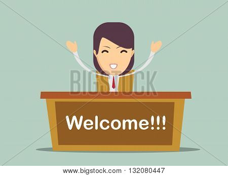Smiling woman sits by the table with welcome word in a close up shot
