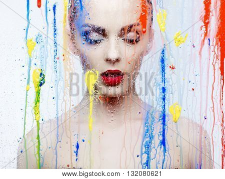 Fashion art studio photo of beautiful model through the glass with bright colors