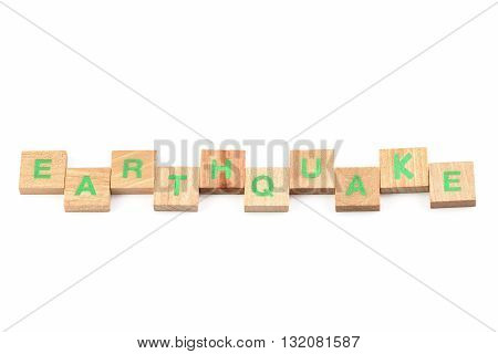 Earthquake written with wooden letters on white background