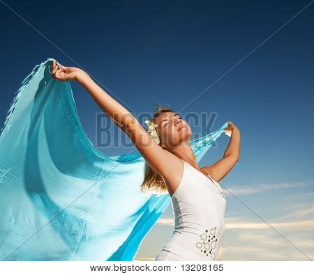 Beautiful young woman with a shawl relaxing outdoors