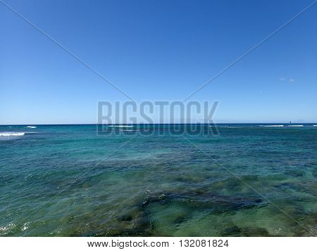 Shallow ocean waters of Waikiki looking into the pacific ocean with a clear blue sky on Oahu.
