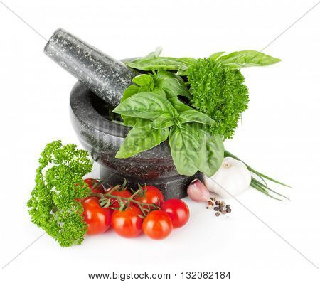 Fresh herbs and spices in mortar and tomato cherry. Isolated on white background