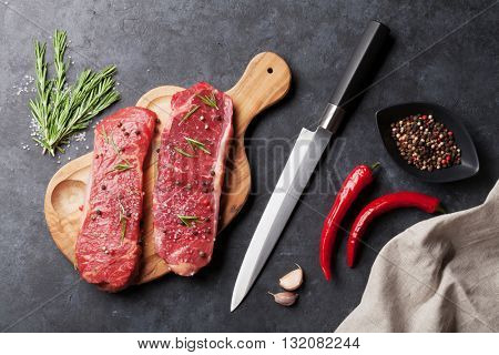 Raw striploin steak with rosemary, salt and pepper cooking over stone table. Top view