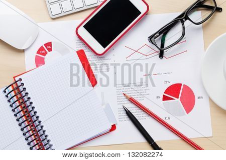 Office desk workplace with smart phone, charts and coffee on wooden table. Top view with copy space