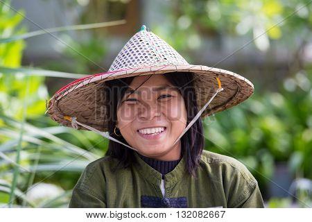 NGAPALI MYANMAR - JANUARY 23 2016: Portrait burmese girl a straw hat in local market. Myanmar Burma